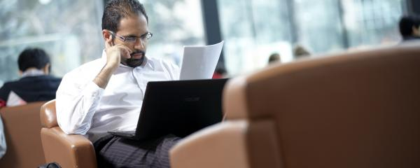 Man looking at paper with a laptop