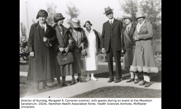 Black and white image of Director of Nursing, Margaret R. Cameron (centre), with guests during an event at the Mountain Sanatorium, 1920s.